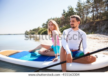 Young couple paddling on sup board with paddle along the beach. Sitting poses, back view - concept of harmony with the nature, free and healthy living, freelance, remote business. - stock photo