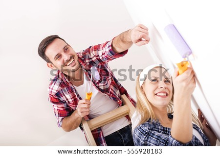 Young Couple Painting A Wall With Roller And Doing Repair At Home Together