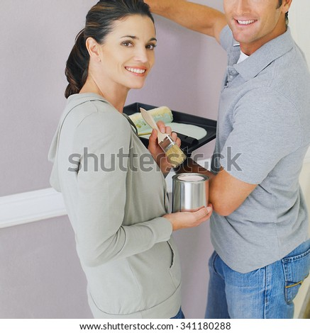 Young couple painting at home working  - stock photo