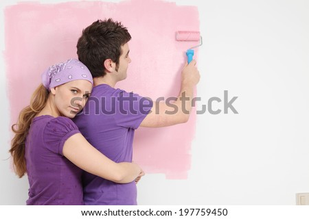young couple painting baby nursery in new home pink - stock photo