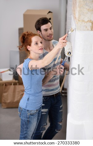 Young couple painting their new home together applying white paint to a wall in a DIY and renovation concept - stock photo