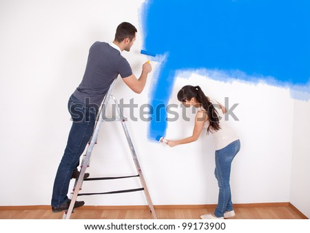Young couple painting wall at home in blue - stock photo