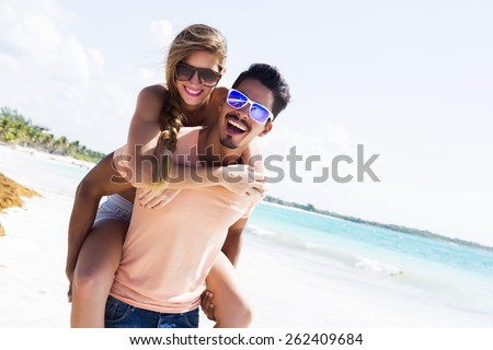 Young couple piggybacking at the beach - stock photo