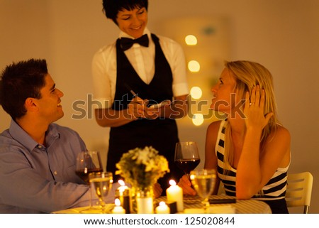 young couple place dinner order to waitress in a restaurant - stock photo