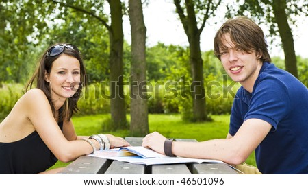 Young couple planning a trip at a picknick table, smiling at the camera - stock photo