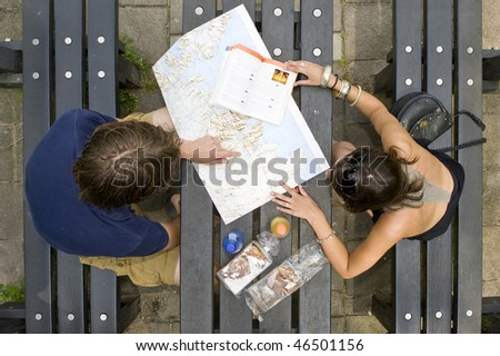 Young couple planning a trip on a map, with a guide book on a pick nick table, with pastries and soda bottles
