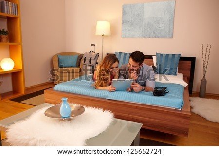 Young couple planning program on holiday while lying on bed in hotel room. - stock photo