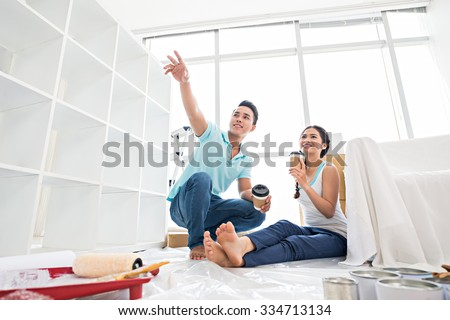 Young couple planning repairs of the new house - stock photo