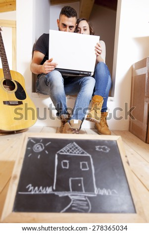 young couple plans to computer the future in new home - stock photo