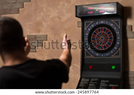Young Couple Playing A Game Shooting Darts - stock photo