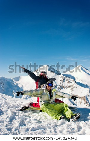 Young couple playing and smiling in the front of beautiful winter background - stock photo