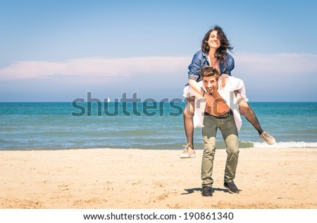 Young couple playing at the beach having fun with a piggyback jump - Happy man and woman at the beginning of a love story - stock photo