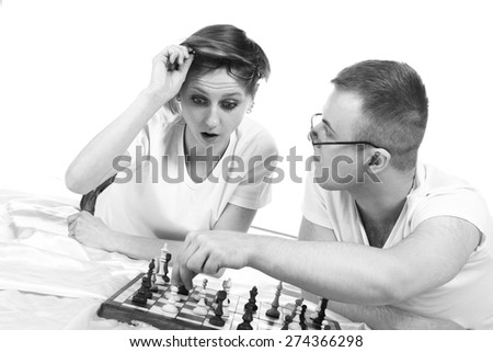 Young couple playing chess, fun emotions