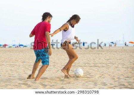 Young couple playing football on the beach at sunset