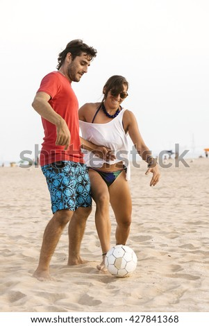 Young couple playing football on the beach at sunset. - stock photo