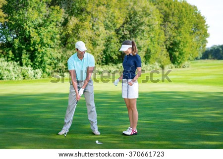 Young couple playing golf