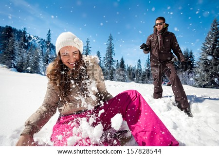 Young couple playing in snow, having snowball fight - stock photo