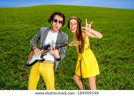 Young couple playing on guitar and enjoying the music, they shout and sing on the green grass background - stock photo