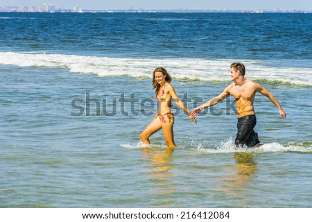 Young couple playing on water in beach. Girl wearing a red, yellow patterned two piece bikini bathing suit, guy wearing a black bathing suit, stretching out arms for each other hands.