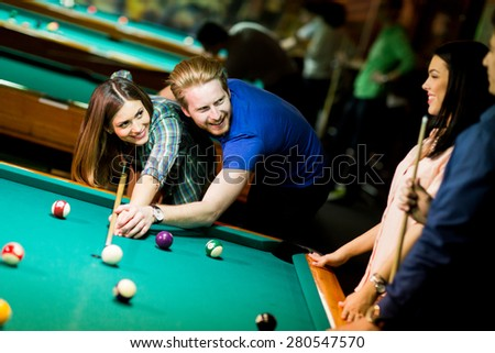 Young couple playing pool - stock photo