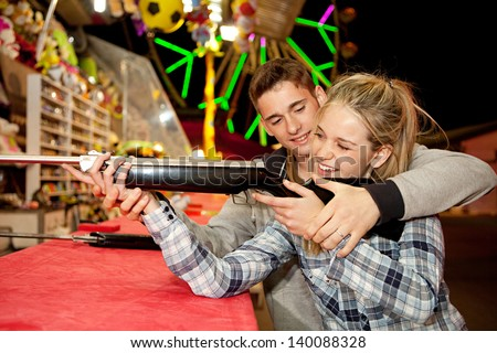 Young couple playing shooting games while visiting an amusement park arcade at night time, having fun with color lights and rides in the background, man helping woman. - stock photo