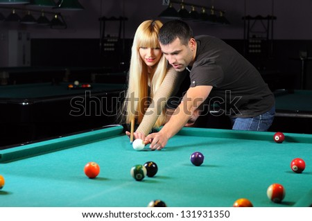 Young couple playing snooker in a billiard club - stock photo