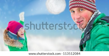 Young couple playing snowball. Winter fun concept