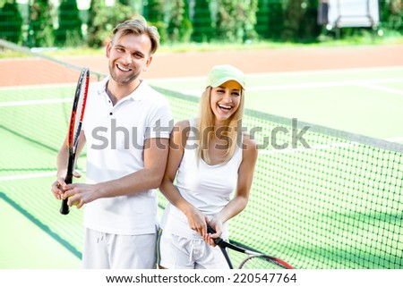 Young couple playing tennis - stock photo