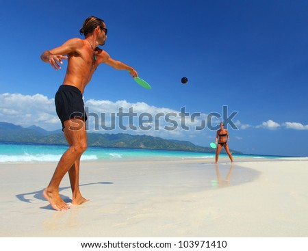 Young couple playing tennis on a beach during their vacation on a tropical island - stock photo
