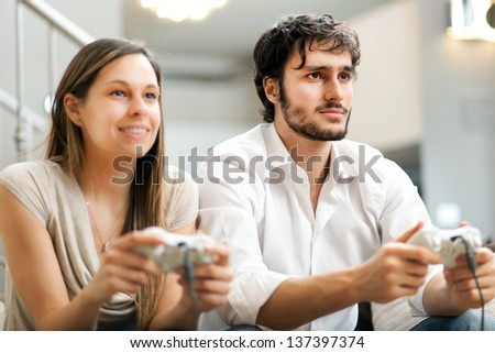 Young couple playing video games in their apartment  - stock photo