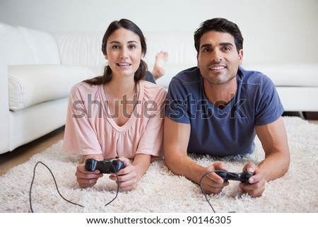 Young couple playing video games in their living room - stock photo