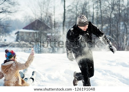 Young couple playing with snow - stock photo