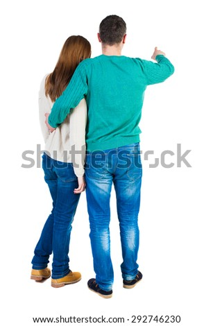young couple pointing at wal Back view  (woman and man). Rear view people collection.  backside view of person.   The guy in the green jacket holding the girl shows her something interesting ahead. - stock photo
