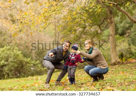 Young couple pointing something to their little boy on an autumns day