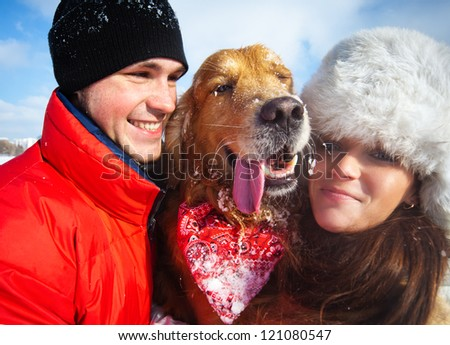 Young couple portrait with winking dog.
