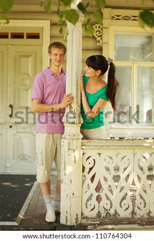 Young couple pose on terrace village house, husband hold on column, focus on girl - stock photo