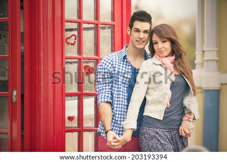 young couple posing against red phone box in Central London - stock photo