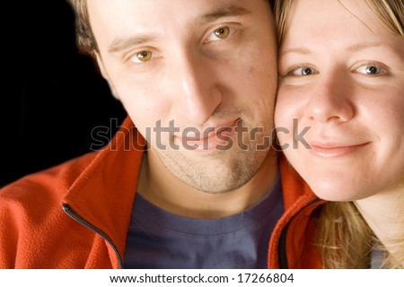 Young couple posing cheek to cheek.