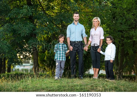 Young couple posing in the park with two kids