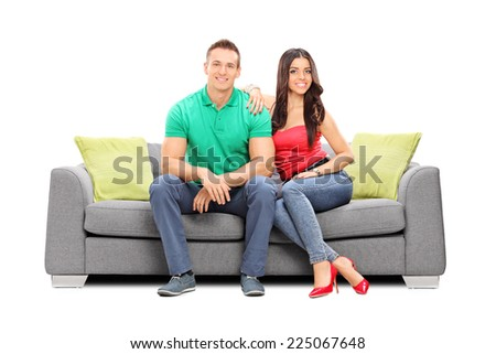 Young couple posing seated on a modern sofa isolated on white background - stock photo