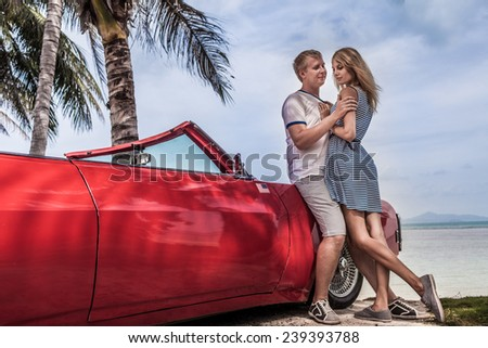 Young couple posing with a red and nostalgic car on tropical beach - stock photo