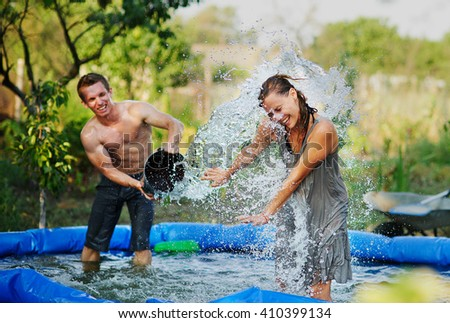 Young couple pours water and fun in summer. Fun summer holidays. Pouring cold water. Ice bucket challenge. Hardening treatment and a healthy lifestyle. Healthy man pours water from a bucket.