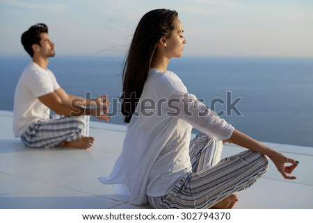 young couple practicing yoga at sunset in modern home terace with ocean and sunset in background - stock photo
