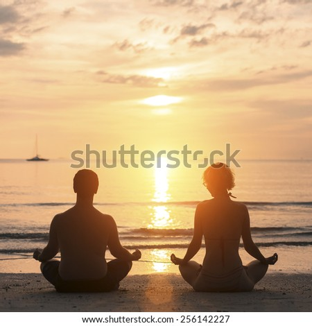 Young couple practicing yoga on Sea beach during sunset.