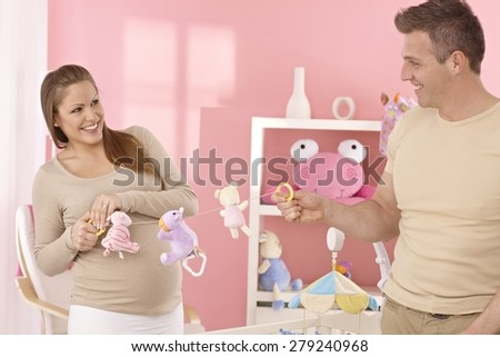 Young couple preparing baby's room, having fun.