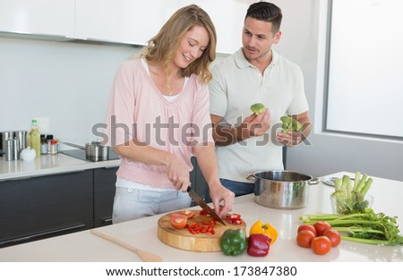 Young couple preparing food together at counter in kitchen