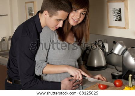 Young couple preparing food together in the kitchen - stock photo