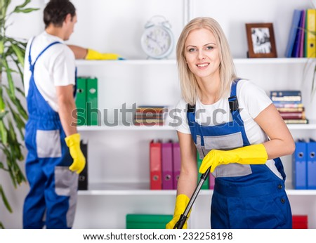 Young couple professional cleaners are cleaning the office. - stock photo