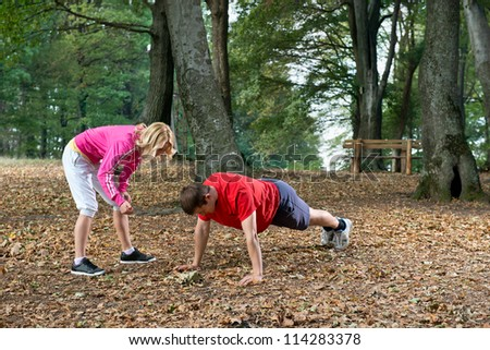 Young couple push-ups in park - stock photo