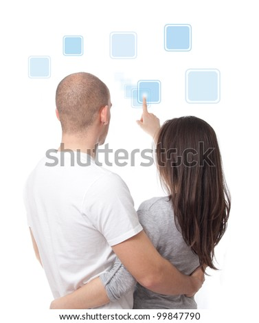 Young couple pushing icons on a touch screen interface - stock photo